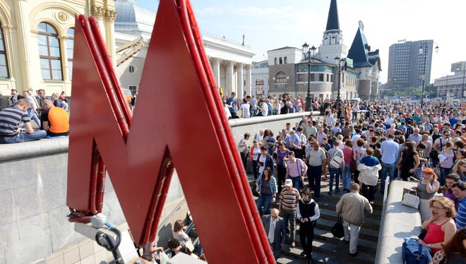 People wait on June 5, 2013, for the reopening of the Komsomolskaya metro station on the red line in Moscow.
