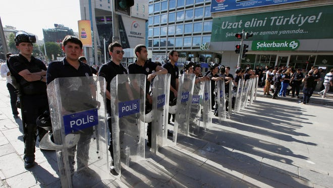 Riot police stand as Turkish youths shout anti-government slogans, in Ankara, Turkey on Tuesday.