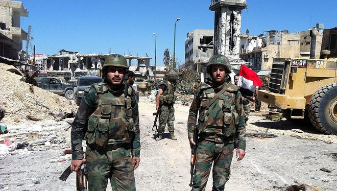 Syrian government soldiers stand  in the main square of the city of Qusayr on June 5 in Homs province. The army claimed it has seized total control of the city and the surrounding region.