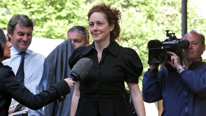 Members of the media gather around former News International Chief Executive Rebekah Brooks as she arrives at a court in London, Wednesday May 5, 2013.