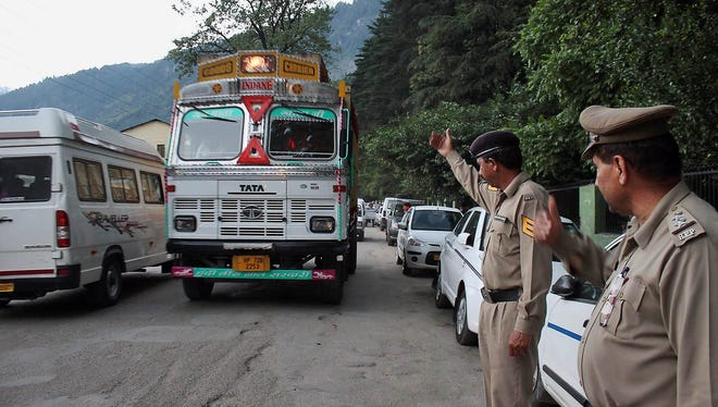 Indian policemen keep a check on vehicles after an American woman was gang-raped  in the northern Indian resort town of Manali, India, June 4, 2013.