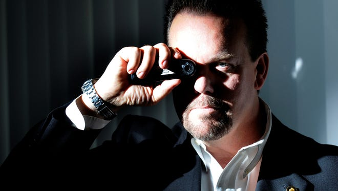 Private detective J.D. LeaSure,  CEO  of ComSec, holds an optical signal identifier.