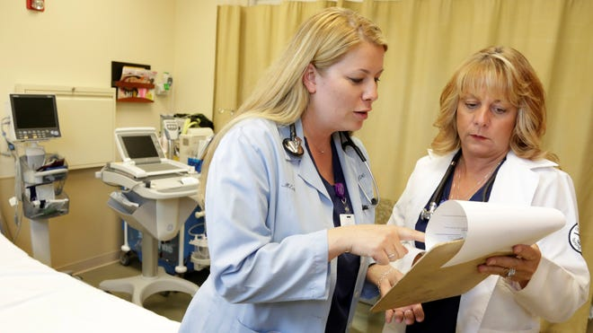 Nurse practitioners Michele Knappe, left, and Julie Zimmer go over a patient's chart at the Ingalls Urgent Aid free-standing emergency room in Flossmoor, Ill.