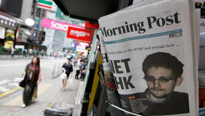 A picture of Edward Snowden, a former CIA employee who leaked top-secret documents about sweeping U.S. surveillance programs, is displayed on the front page of South China Morning Post at a news stand in Hong Kong on June 13, 2013.