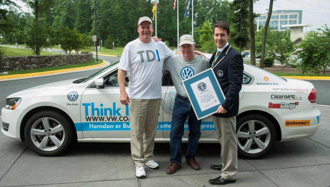 Making their 78 mpg record in a VW Passat diesel official, driving team Wayne Gerdes, left, and Bob Winger get certificate from Guinness World Records adjudicator Philip Robertson at VW's U.S. headquarters in Herndon, Va.,