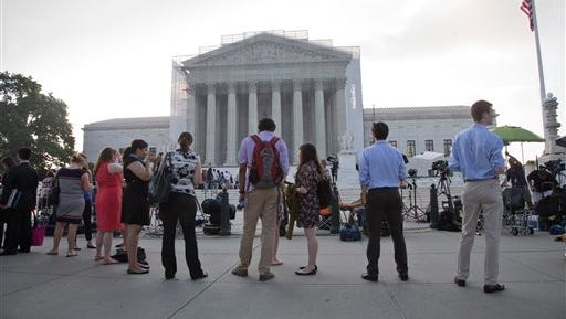 People wait outside the Supreme Court in Washington as key decisions are announced Monday, June 24, 2013.