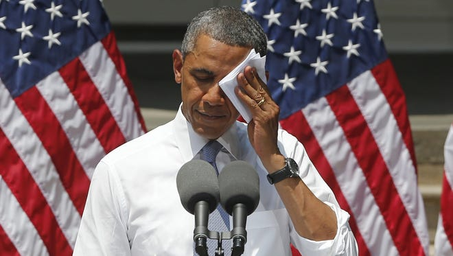 President Obama wipes his face as he speaks about climate change, June 25, 2013, at Georgetown University in Washington.
