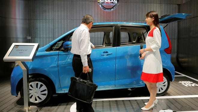 A shopper, left, looks at a Dayz hatchback at a Nissan showroom in Tokyo on Tuesday as CEO Carlos Ghosn spoke to shareholders.