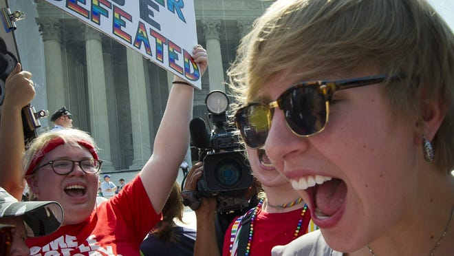 Gay rights activists react outside the US Supreme Court Wednesday.