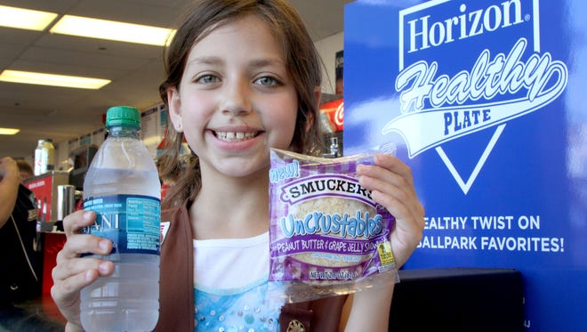 Rachel Walters, 7, of Point Pleasant, N.J., shows off her peanut butter and Jelly and bottled water at FirstEnergy Park in Lakewood, N.J., home of the BlueClaws minor league baseball team.