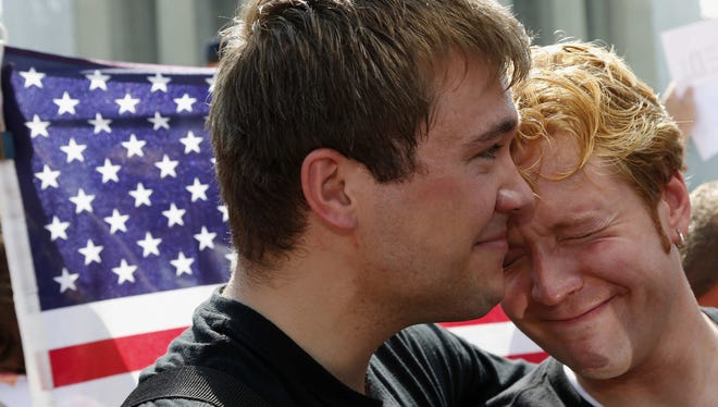 Michael Knaapen, left, and his husband John Becker embrace outside the Supreme Court Wednesday.