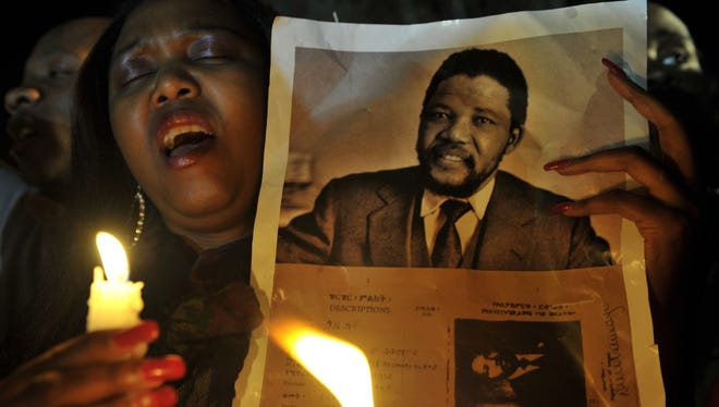 A woman holds a candle and a photo of Nelson Mandela as she prays for his recovery outside the hospital where he is being cared for in Pretoria, South Africa, on June 27.