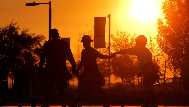 Construction workers gather at a new home site at sunrise to beat daytime high temperatures on June 27, 2013, in Queen Creek, Arizona.