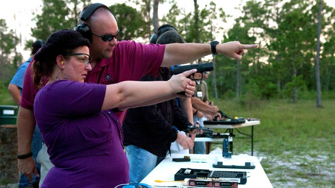 Michelle Shin of Naples, Fla., aims at a target during a concealed weapons class with instructor Keith Hanson in north Collier County, Fla., on July 9, 2012.