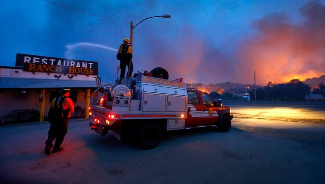 Firefighters protect a restaurant from flames in the area of  Glenn Ilah near Yarnell on Sunday.  Nineteen firefighters have died in the Yarnell Hill Fire.