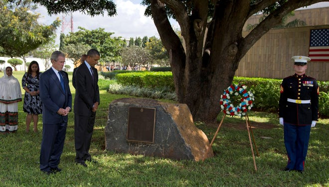 President Obama and former president George W. Bush pause for a moment of silence during a wreath-laying ceremony to honor the victims of the U.S. Embassy bombing in Tanzania.