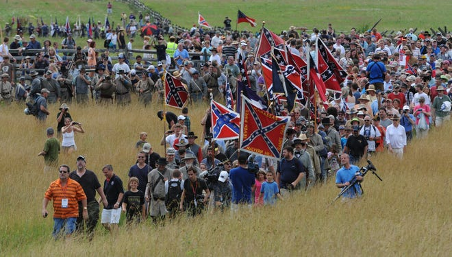 Re-enactors and visitors walk across the Gettysburg Battlefield in a commemoration of Pickett's Charge.