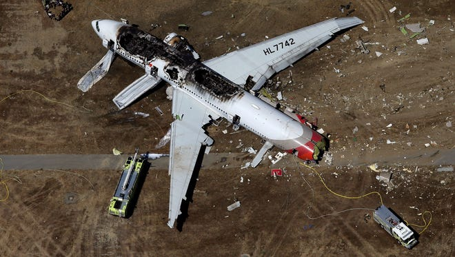 A Boeing 777 airplane lies burned on the runway after it crash landed at San Francisco International Airport July 6, 2013.
