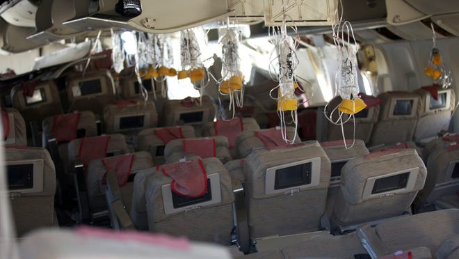 Oxygen masks hang from the ceiling in the cabin  of Asiana Airlines Flight 214.