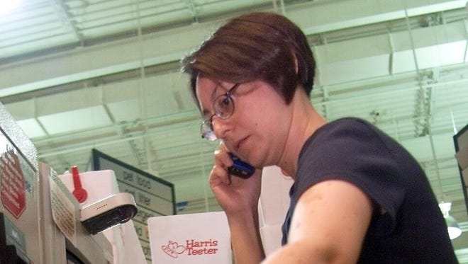 Dawn Worrell of Arlington, Va., talks on her cell phone while checking-out herself out at Harris Teeter.