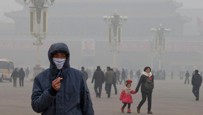 A man wears a mask on Tiananmen Square in thick haze in Beijing on Tuesday, Jan. 29, 2013. Extremely high pollution levels shrouded eastern China for the second time in about two weeks.