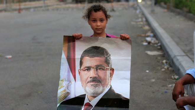 A supporter of ousted Egypt President Mohammed Morsi poses with his photo as army soldiers stand guard at the Republican Guard building in Nasr City, in Cairo, Egypt, on July 10, 2013.