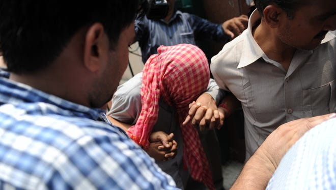 Indian policemen in plain clothes escort the juvenile accused, center, in the New Delhi gang rape case as he leaves The Juvenile Justice Board building in New Delhi on July 11, 2013.