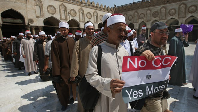 An Egyptian cleric and a supporter of ousted Egypt's President Mohammed Morsi hold up a placard against Egyptian Defense Minister General Abdul Fatah al-Sisi, as they leave with other clerics following a  protest, at al-Azhar mosque in Cairo on July 14, 2013.