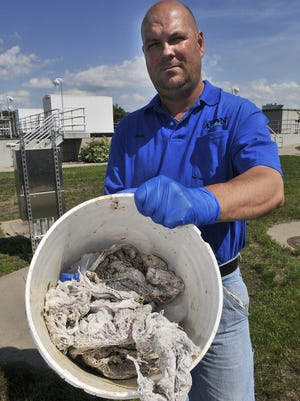 Jon Forsell, utilities superintendent for Avon, Minn., shows some of the debris containing disinfectant wipes that they've had to pull out of the city's sewer lift station pumps.