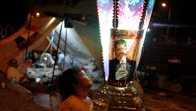 A boy stands near a traditional lantern, marking the Islamic month of Ramadan, with a poster of Egypt's ousted President Mohammed Morsi in a park in front of  Cairo University, late Tuesday.
