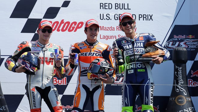 Marc Marquez of Spain, center, celebrates with Stefan Bradl of Germany, left, who finished second, and Valentino Rossi of Italy, who finished third Sunday at Laguna Seca.