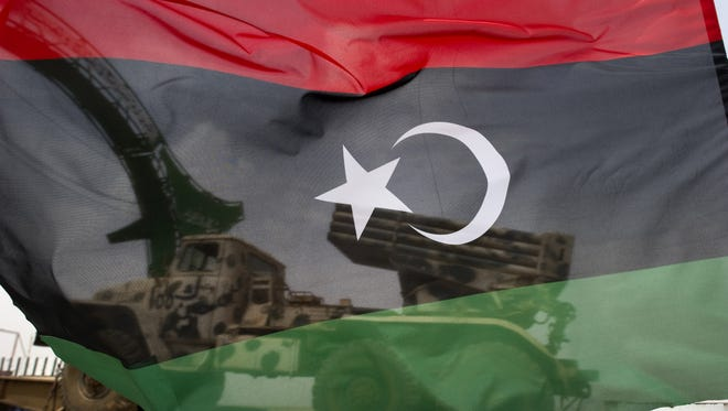 A rebel lorry with a rocket launcher is seen through a the Libyan rebellion's flag.