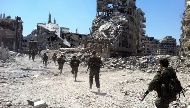 Syrian government forces patrol in the Khalidiyah neighborhood of the city of Homs on July 28.