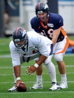 Denver Broncos  center Manny Ramirez (66) prepares to snap the ball Peyton Manning during practice July 29, 2013, in Englewood, Colo.