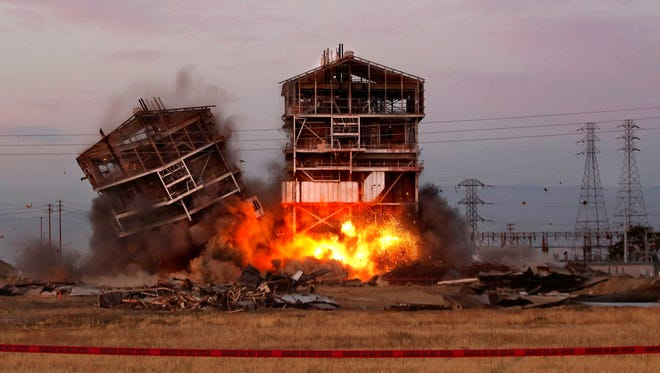 An explosion knocks down one of the remaining towers at the old Kern Power Plant on Saturday in Bakersfield, Calif.