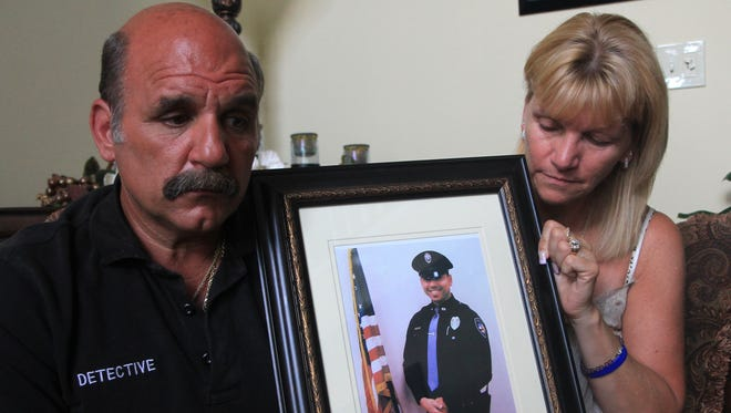 Joe and Pat Engrassia hold picture of Pat's son, Jason Marles. Marles was an Ocean Gate, N.J., police officer killed in a car accident in 2010. Robert Ward / Staff Photographer