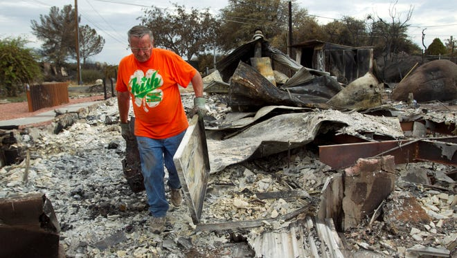 Arvid Burnham carries away debris July 10, 2013, of what was his home in Glen Ilah, Ariz. The Yarnell Hill Fire destroyed it June 30.