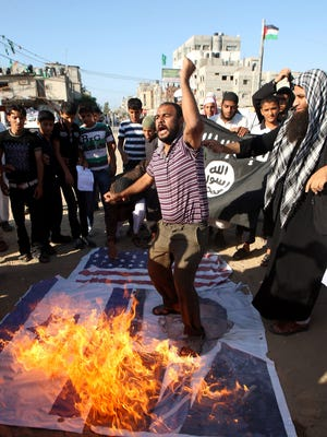 In Gaza, Palestinians protesting an anti-Islam film in September burn a picture of President Obama and American and Israeli flags.