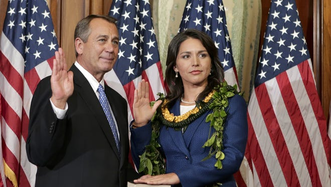 Rep. Tulsi Gabbard, D-Hawaii, stands for a ceremonial photo with Speaker of the House John Boehner on Thursday.