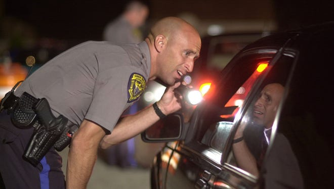 Dover Twp. Patrolman Tim Sysol talks to a motorist at D.U.I checkpoint on Fischer Blvd. in Toms River, NJ.