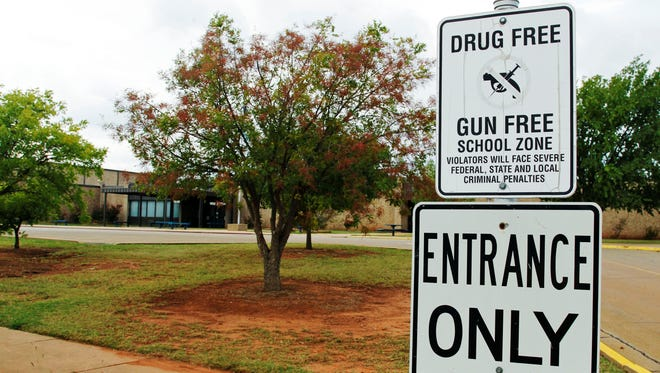 A sign declaring a junior high school as a drug-free and gun-free zone.