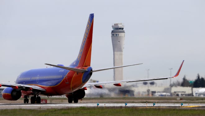 A jet waits to depart in view of the air traffic control tower at Seattle-Tacoma International Airport.