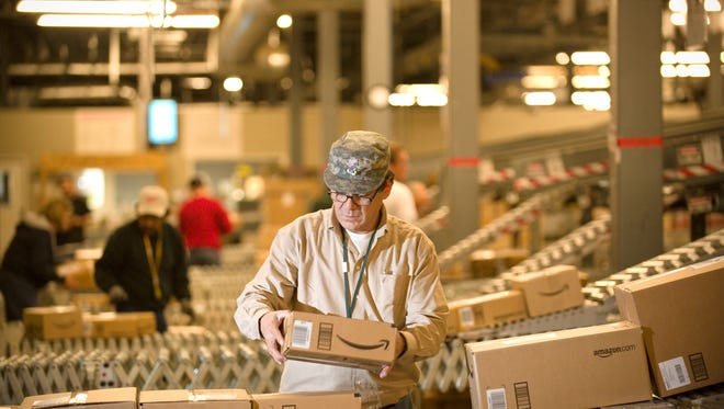 An Amazon.com employee grabs boxes off the conveyor belt to load in a truck in Fernley, Nev.