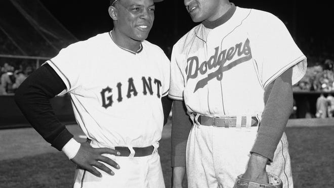 Willie Mays, left, and Don Newcombe, both returned from military service, pose together on opening day at the Polo Grounds in New York on April 13, 1954.