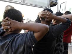 Illegal immigrants prepare to enter a bus after being processed at Tucson Sector U.S. Border Patrol Headquarters Aug. 9.
