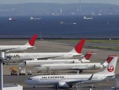 Japan Airlines planes park on tarmac of Tokyo's Haneda Airport.