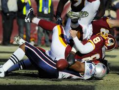 Washington Redskins quarterback Rex Grossman fumbles the ball as he is sacked in the end zone by New England Patriots defensive end Andre Carter on Dec. 11, 2011. Carter had a tryout with the Cardinals Tuesday, but didn't get an offer.
