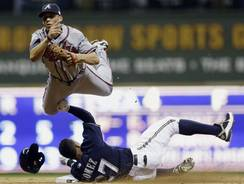 The Braves' Andrelton Simmons leaps over the Brewers' Carlos Gomez while trying to turn a double play during the seventh inning.