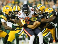 Bears running back Matt Forte (22) is stopped by Packers defenders during the first quarter at Lambeau Field.