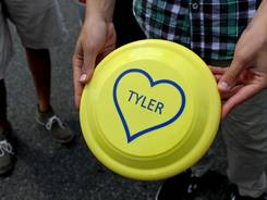 Brett Pogostin, 16, of Scarsdale, N.Y., holds a Frisbee given to guests in honor of Tyler Madoff, 15, at a memorial service in New Rochelle, N.Y., on July 26.